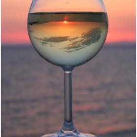 В чаша вино залез и небе, а за фон море!