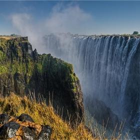 Виктория е на територията на Зимбабве и Замбия. Туристите отсреща се наслаждават на водопада от Зимбабве.