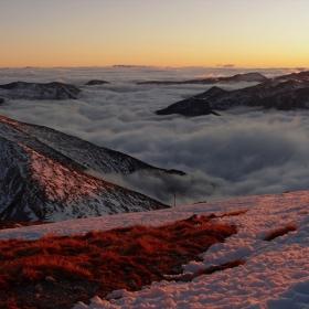 Море от сребърна мъгла покрива  с вълни лазурни от залязващото слънце долината